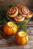 Orangefarbene Pomanderkugeln mit Kerzen und Zimtrollen