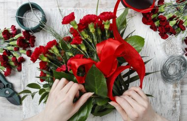 Florist at work. Woman making bouquet of red carnations