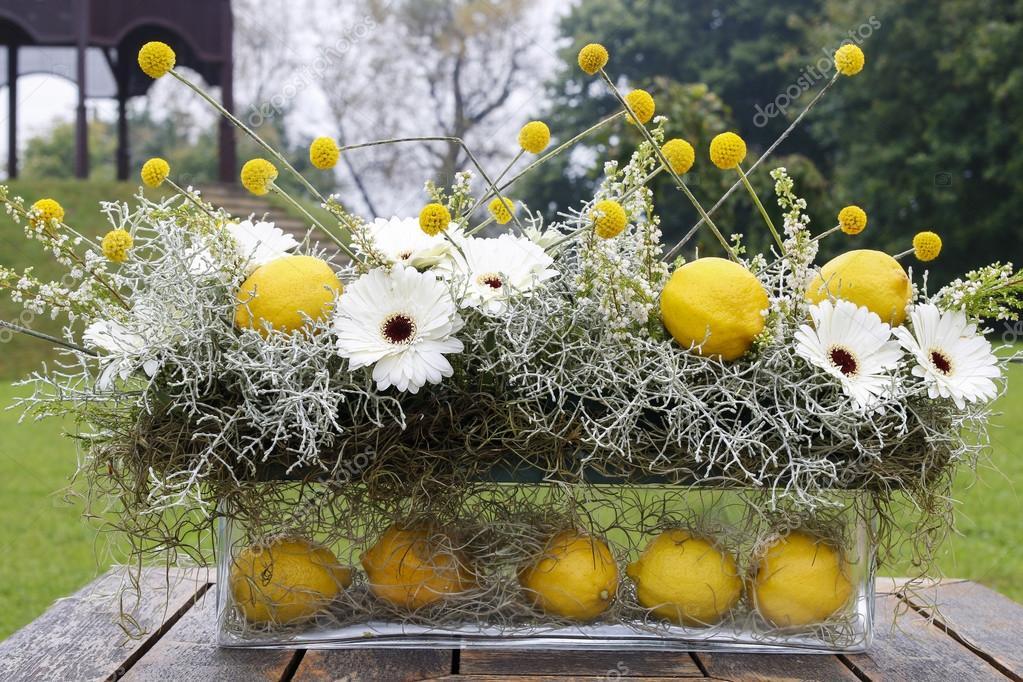 Moderne Blumen Gesteck mit weißen Gerbera Blumen und Zitrone f ...