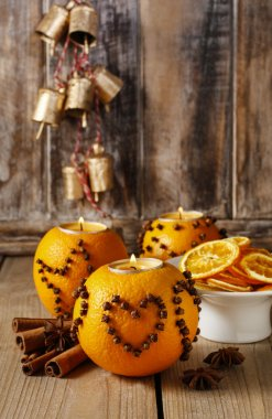 Orange pomander ball with candle decorated with cloves in heart
