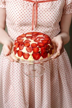 Woman holding strawberry cake on cake stand