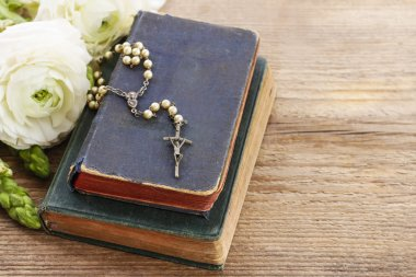 Holy Bible and white rosary.