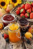 Fotografia Pesca, mirtillo e fragola marmellate in barattoli di vetro