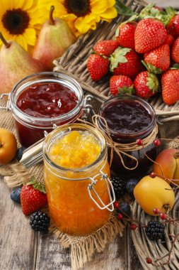 Peach, blueberry and strawberry jams in glass jars