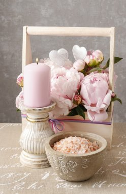 Wooden box with pink peonies, scented candle and bowl of sea sal