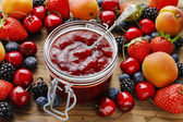 Photo Jar of strawberry jams among summer and autumn fruits