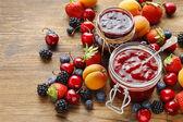 Photo Jar of strawberry jams among summer and autumn fruits
