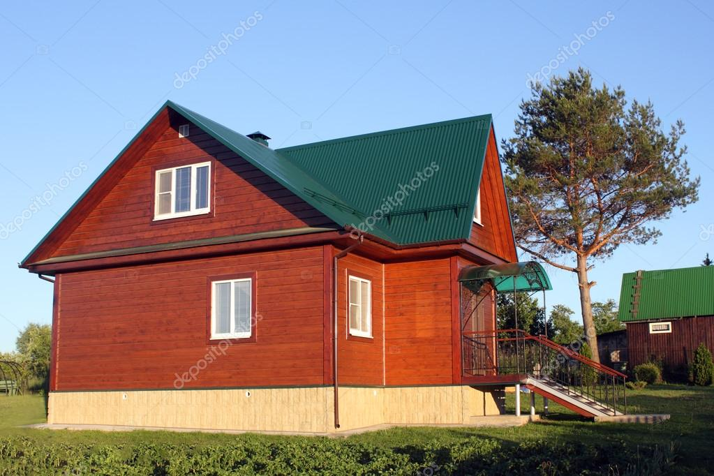 Wooden house under green metal roof