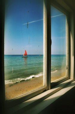 View from the window of an old thrown house on a boat with red s