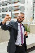 Mladí rádi vousatý podnikatel stojící mimo kancelářská budova
