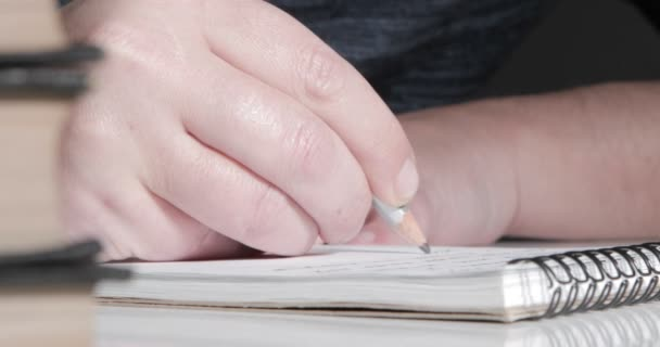 A male hand writing notes in notepad
