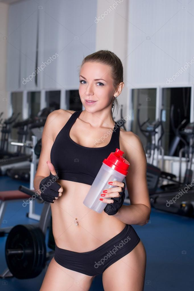 Strong fitness girl with cocktail bottle after workout in for Cocktail fitness