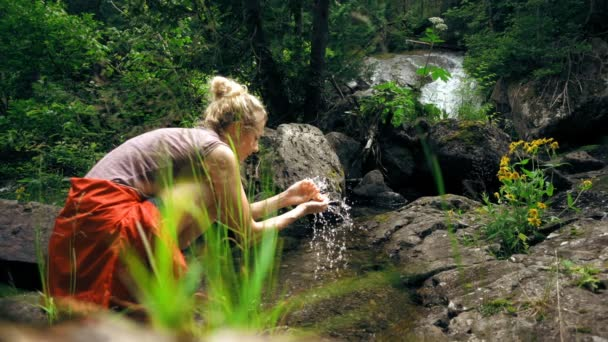 Woman washing her Hands in Stream