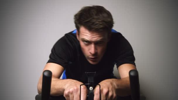 Motivált fiatalember futásnak és izzadás, helyhez kötött kerékpár