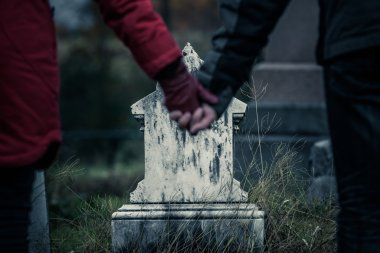 Brother and Sister Holding Hands in front of  Gravestone