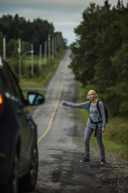 Woman Hitchhiking on the Side of the Road