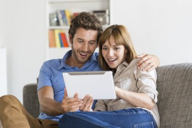 Young couple surfing on internet with tablet pc on sofa at home