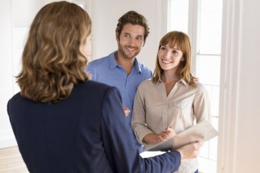 Young couple visiting apartment with real estate agent