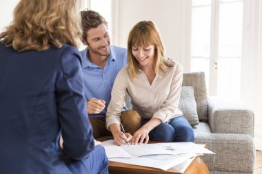 Young couple owners signing a contract with real estate agent for house purchasing