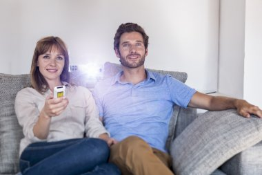 Couple watching a movie with a video projector, on couch