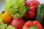 Hintergrund ist saftig reifes und schmackhaftes Gemüse. Gelbe und rote Tomaten, rote Paprika, Rucola, Salat, Gurken.