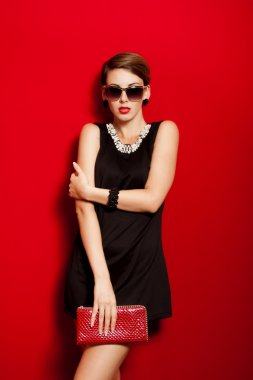 Beautiful girl with a red clutch bag in her hands