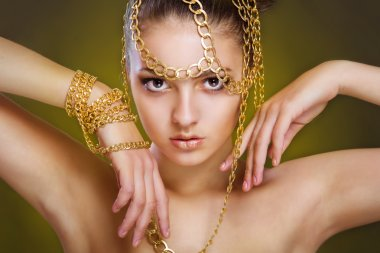 Girl with golden make-up and decoration of gold
