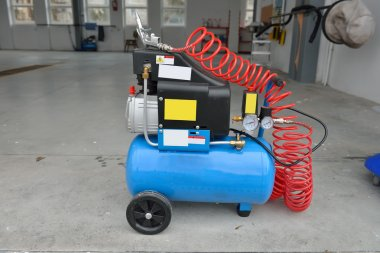 Blue pump compressor for washing cars, indoor. Cleaning concept.