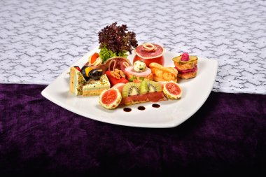 Antipasto and catering platter with different appetizers (fruits