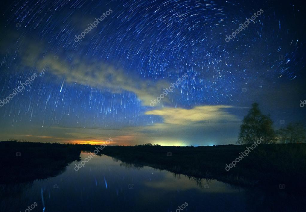 A beautiful night sky, the Milky Way, spiral star trails and the trees