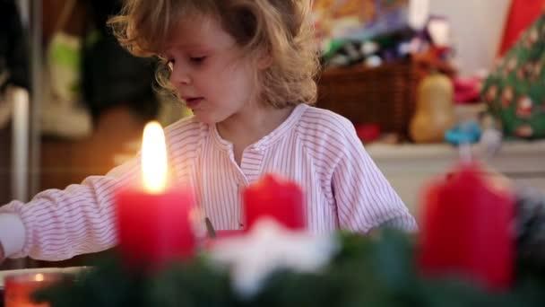 Kerze mit Kind im Hintergrund am ersten Advent