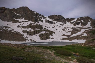 Wide view of Cony Lake elevation 11,512', in Rocky Mountain National Park in summer. Part of the lake is still frozen, with Ogalalla and Copeland Mountains in the background