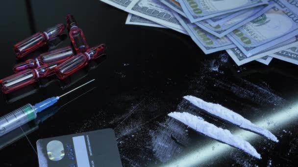 Addicted man is using drugs through rolled US dollar bill. Male sniffs cocaine white powder drug using dollar tube. Addict takes dose of drugs. Cocaine being snorted off glass surface with straw
