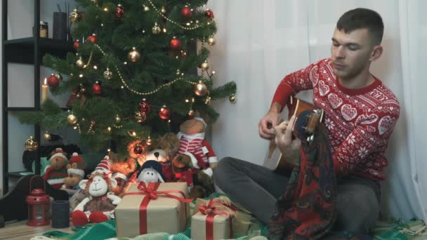 Young man is playing acoustic guitar sitting near Christmas tree and singing songs, celebrating New Year 2021 alone at home. Christmas spirit, holiday and celebration concept