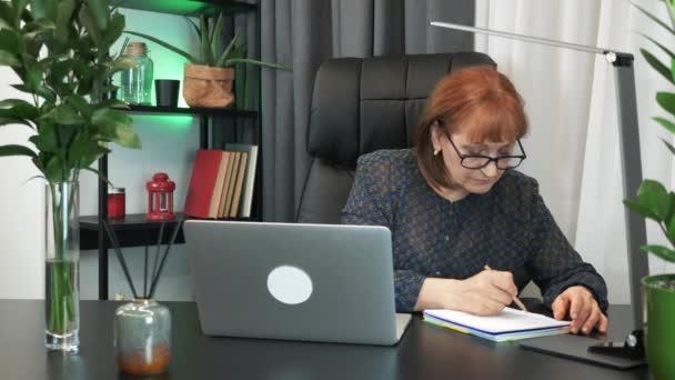 Multitasking na pracovišti v kanceláři. Podnikatelka dělá hodně věcí, když sedí v moderní kanceláři. Žena pracuje na notebooku v kanceláři, dělá si poznámky a píše na klávesnici