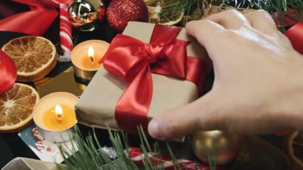 Vánoční dárek a dekorace. Osoba umísťuje zabalený dárek do vánoční dekorace pozadí před Vánocemi. Šťastný Nový rok2021. Vánoční pozadí s dárkovou krabicí