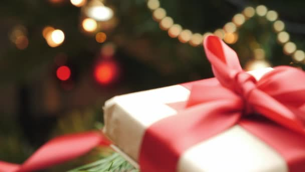Zabaleno do řemeslného papíru s červenou stuhou Vánoční dárek pod stromečkem. Vánoční a novoroční dekorace. Prázdninový dárkový box s výzdobou