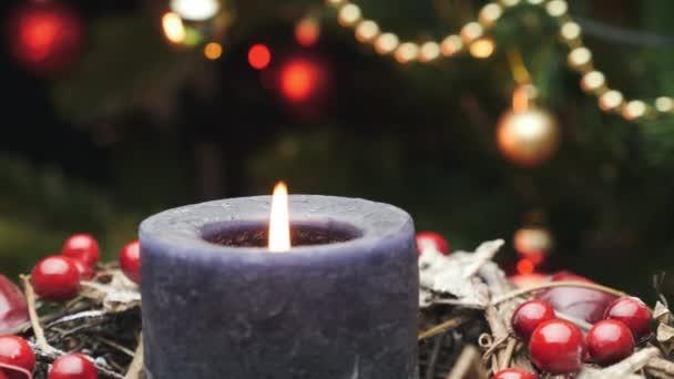 Schön geschmückter Weihnachtstisch mit Kerze gegen Weihnachtsbaum. Lit Weihnachtskerze in traditionellen Weihnachtskranz. Neujahrsdekoration, Feier