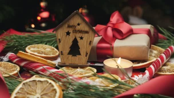 Frohe Weihnachten Figur auf buntem Dekorationshintergrund. Schöne Neujahrsdekoration mit Geschenken und brennenden Kerzen. Heiligabend feiern