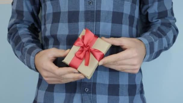 Ruce drží malou zabalenou dárkovou krabičku se svázanou mašlí, zblízka. Neznámé mužské ruce ukazují dárek. Svatý Valentýn a koncept dovolené