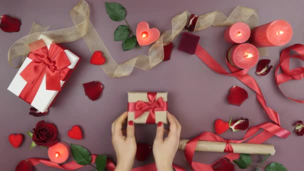 Hands are taking wrapped gift box with tied red bow for St. Valentines Day. Female takes present gift for 14th of February from table with roses, burning candles and gifts on red background