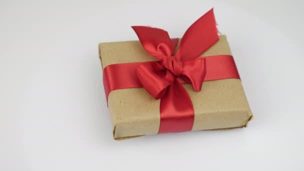 Na bílém pozadí se otáčí zabalená dárková krabice s červenou stuhou přivázanou mašlí. Valentýnské svátky dárek překvapení. Dárek s červenou mašlí na Valentýna nebo narozeniny. Romantický pozdrav