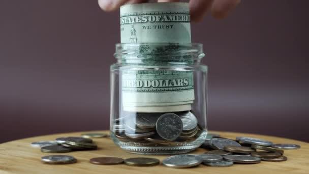 Ruční vkládání srolovaných bankovek v amerických dolarech do sklenice. Koncept spoření