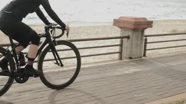 Cycling on promenade. Cyclist in black cycling outfit is riding bicycle on sea quay