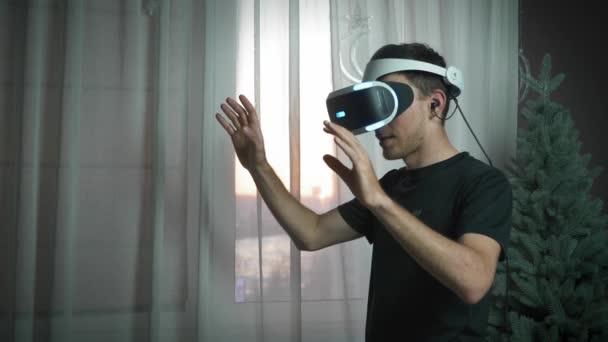 Mann trägt VR-Brille, gestikuliert und sieht etwas in Augmented Reality