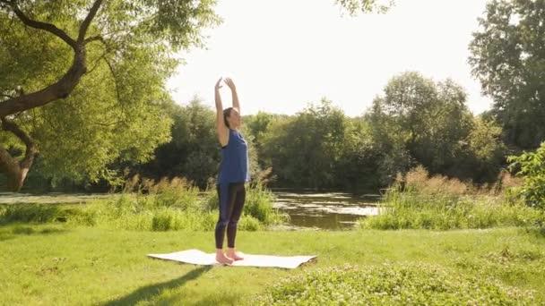 Žena ráno cvičí v parku. Žena dělá meditační cvičení při východu slunce