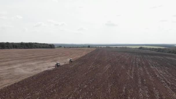 Zemědělské stroje orají pole po sklizni. Traktory pracující na poli