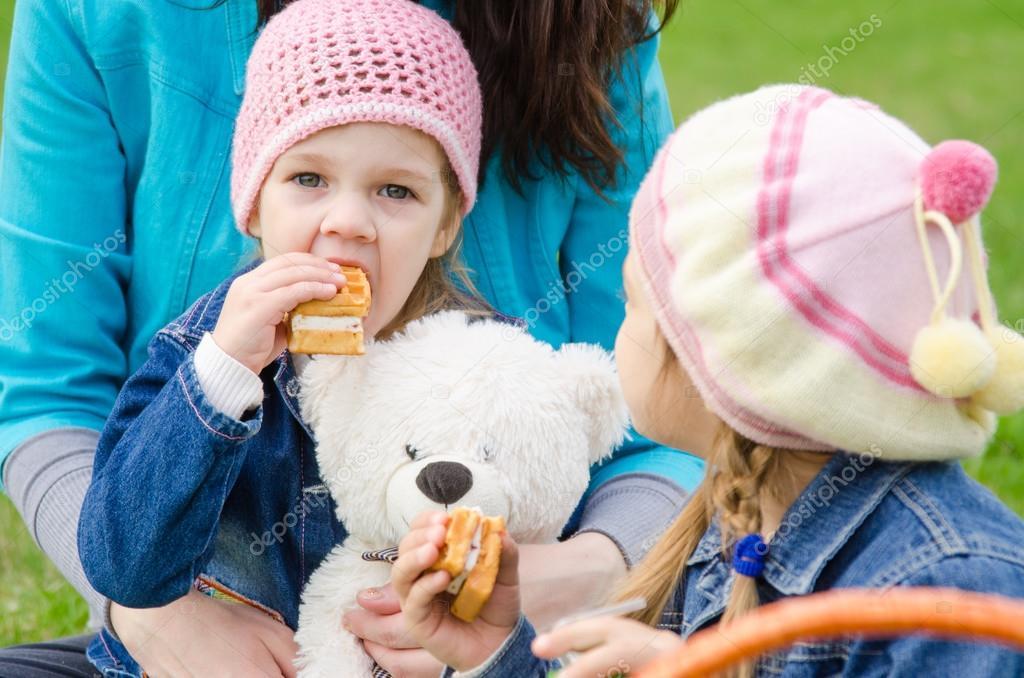 Маленькая девочка на улице ест банан и смеется. — Стоковое