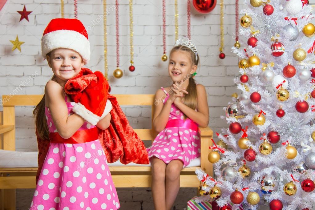 Mädchen verkleidet als Weihnachtsmann, die Geschenke in der Tasche ...