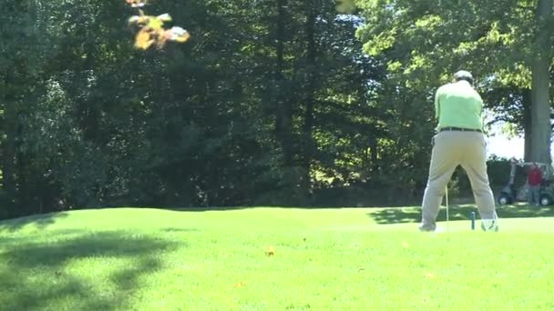 Golfer swings with driver to hit ball